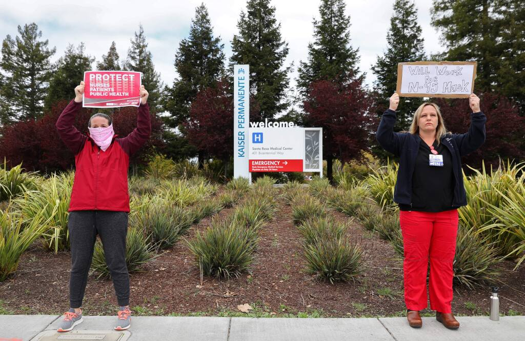 Registered nurses Melissa L., left, who did not want to provide her last name, and Chelsea Carrera protest the shortage of personal protective equipment supplied to public health workers at Kaiser Permanente, in Santa Rosa on Monday, March 23, 2020. (Christopher Chung/ The Press Democrat)