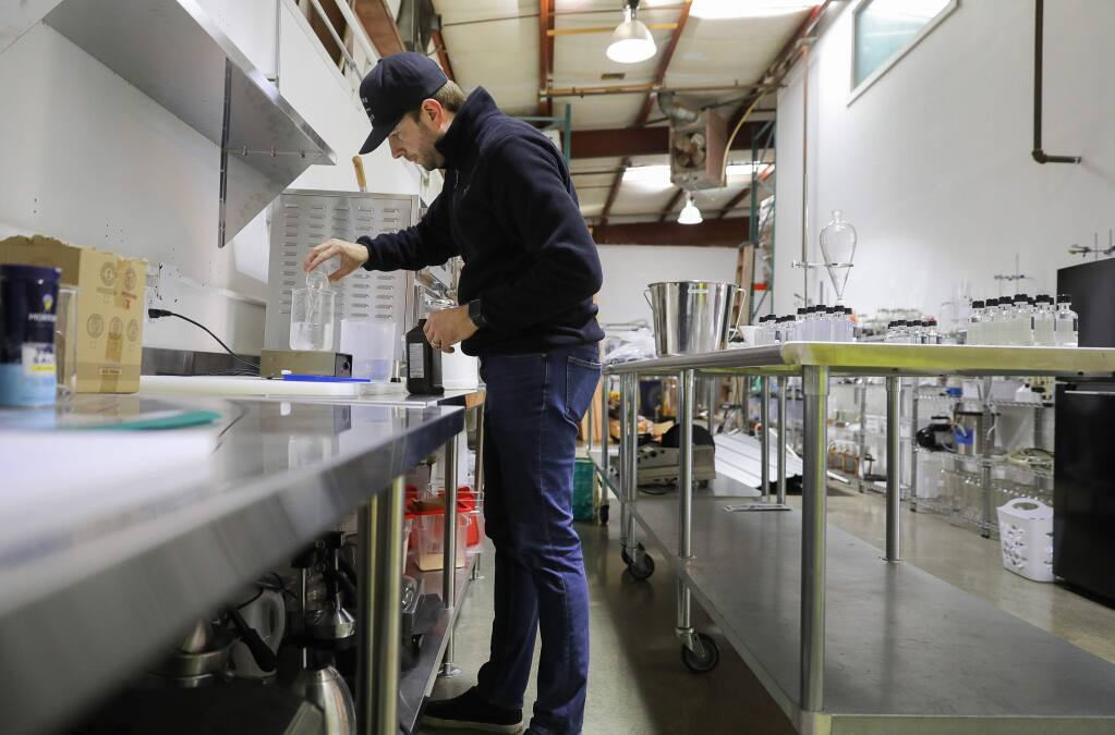 Josh Opatz, co-founder of Young & Yonder Spirits, uses alcohol made at his Healdsburg distillery to make hand sanitizer, on Tuesday, March 24, 2020. Opatz is giving the hand sanitizer away for free to the local community. (Christopher Chung/ The Press Democrat)