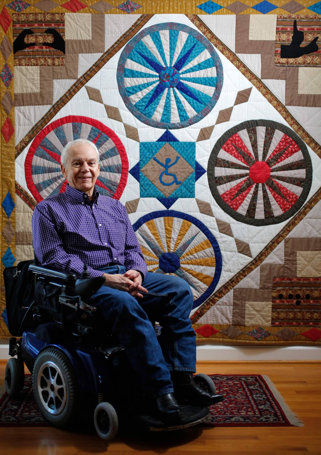 Disability advocate Anthony Tusler in front of a disability-themed quilt at his home in Penngrove on Friday, Nov. 6, 2015. (Alvin Jornada / The Press Democrat)
