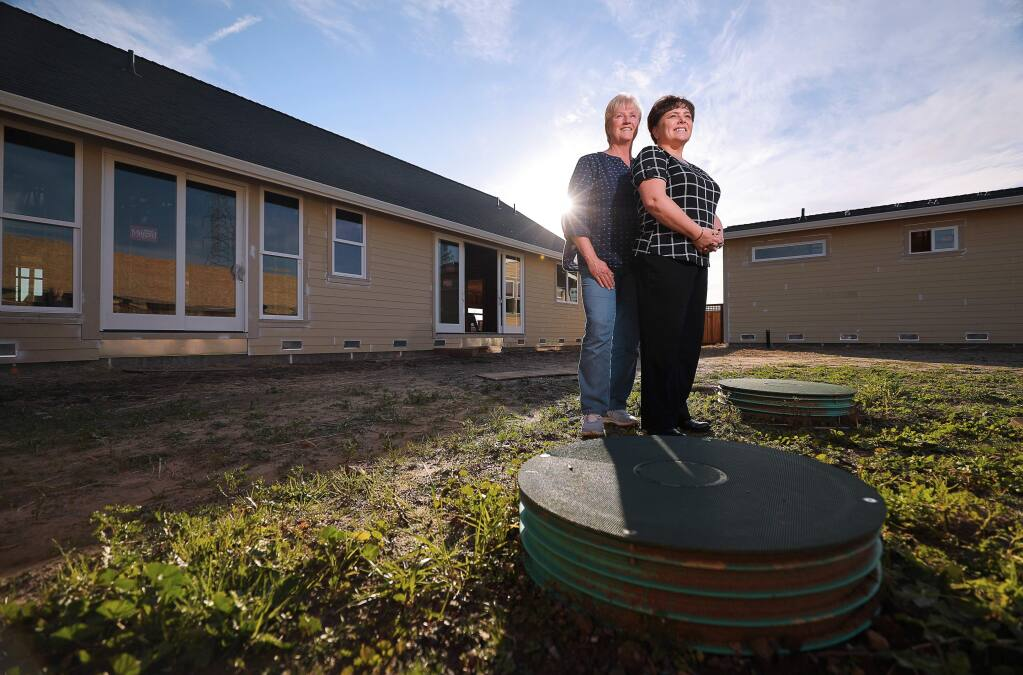Gena, right, and Sheri Jacob stand above their septic system in the backyard of their rebuilt home in Larkfield. Their home will be tied into a new sewage system in 2020. Gena is one of the Larkfield Estates residents who spearheaded an effort to establish a sewer system in the unincorporated neighborhood in the aftermath of the Tubbs fire. (Christopher Chung/ The Press Democrat)