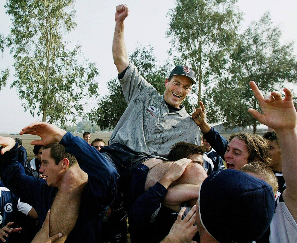 SRJC men's soccer coach Marty Kinahan is hoisted by players after their 3-2 victory to win the state championship. (Gary Kazanjian)