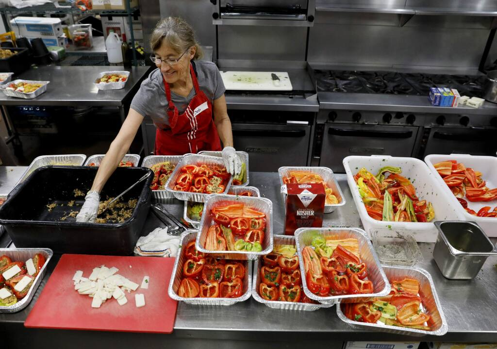 Deborah Cutler, a volunteer with Sonoma Family Meal, puts together stuffed bell peppers to be cooked in the kitchen of the Vintners Inn in Fulton, on Tuesday, October 24, 2017. (BETH SCHLANKER/ The Press Democrat)