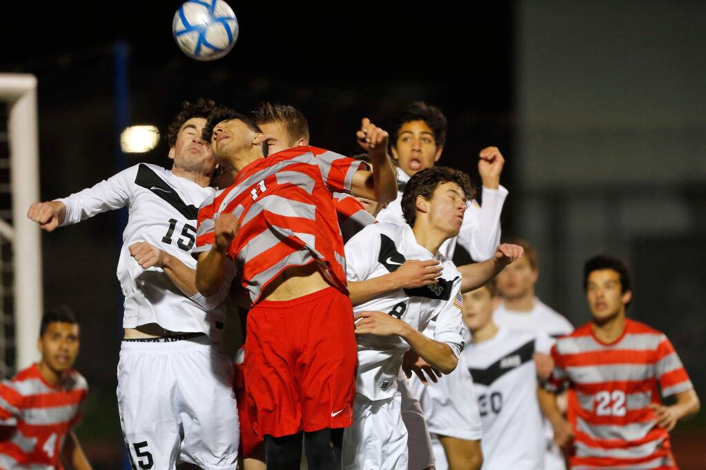 Montgomery's Primitivo Pardo (11), second from left, tries to get a header into the goal past Acalanes' Nick Schirmer (15), left, during overtime in the NCS Division 2 boys varsity soccer championship match in Lafayette on Saturday, February 25, 2017. (Alvin Jornada / The Press Democrat)