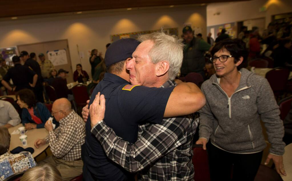 Mark Mollet, an Orange County fire captain, hugs Jeffrey Rothman of Santa Rosa, as Mollet and other firefighters are applauded as they arrive to enjoy a 'A Thousand Thanks Pancake Breakfast' presented by Boys Scouts Troop 32 at the Church of the Roses in Santa Rosa, Calif., on Saturday, October 21, 2017. (Photo by Darryl Bush / For The Press Democrat)