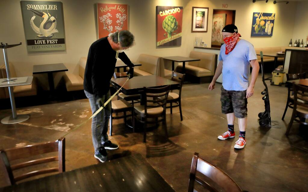 Rosso Pizzeria owner Kevin Cronin, left, and general manager Richie Hovden use a tape measure to distance out tables, Tuesday, May 12, 2020 in response to an announcement that restaurants can open up with social distancing and other precautions in the coming days. They are also planning to install plexiglas between the booths. (Kent Porter / The Press Democrat) 2020