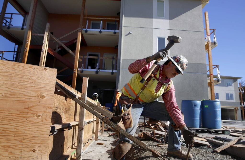 (FILE PHOTO) Salvador Preciado of R.E. Maher Inc. builds a wooden frame for a concrete wall to be poured amid work on the Fetters Apartment complex outside of Sonoma on Wednesday, November 16, 2016. Sonoma County officials are working to fast track higher density housing options outside cities. (BETH SCHLANKER/ The Press Democrat)