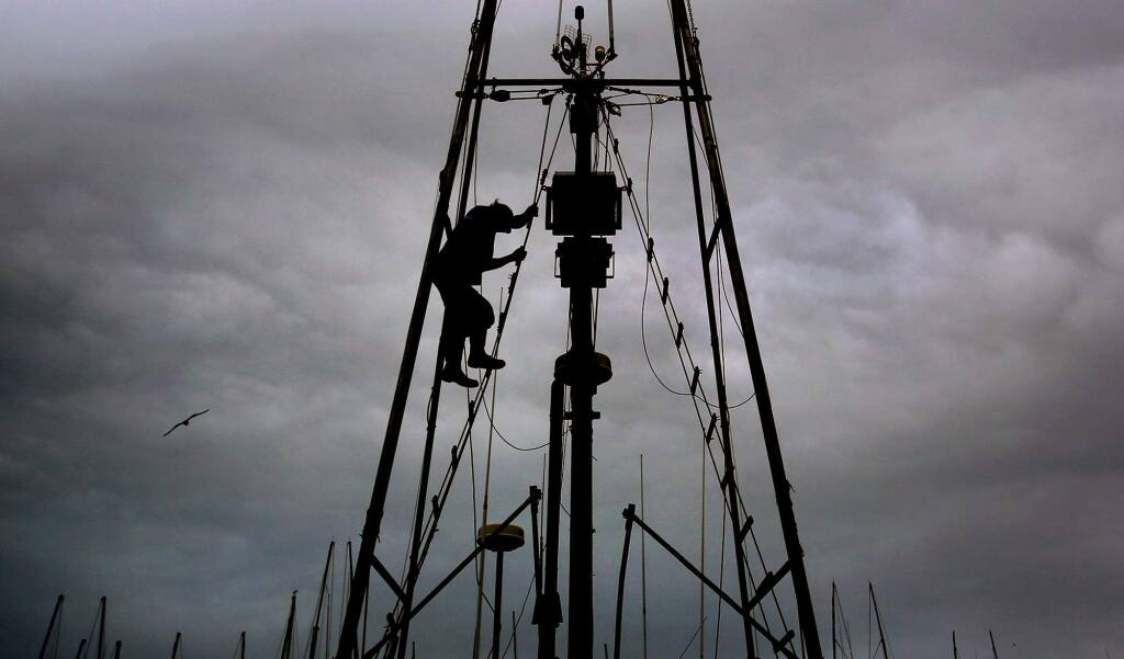 Deckhand Mike Duer on the Sandy B, captained by Stan Carpenter, descends rigging after adjusting an antenna, Thursday April 6, 2017 at Spud Point Marina in Bodega Bay. The fleet is taking another hit as salmon season looks to be delayed. (Kent Porter / The Press Democrat) 2017
