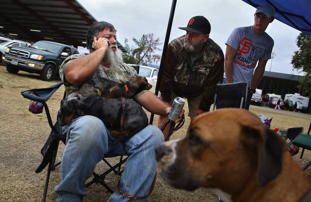 Larry Fleming, left, talks on the phone with a friend inside the Valley fire zone, while Patrick Granzotto and his son, Forrest, wait to hear news on their Middletown home, at the evacuation center in Calistoga, on Monday, September 14, 2015. Fleming's contact was able confirm the Granzotto's home was still standing and fed their pot-bellied pig for them.(Christopher Chung/ The Press Democrat)