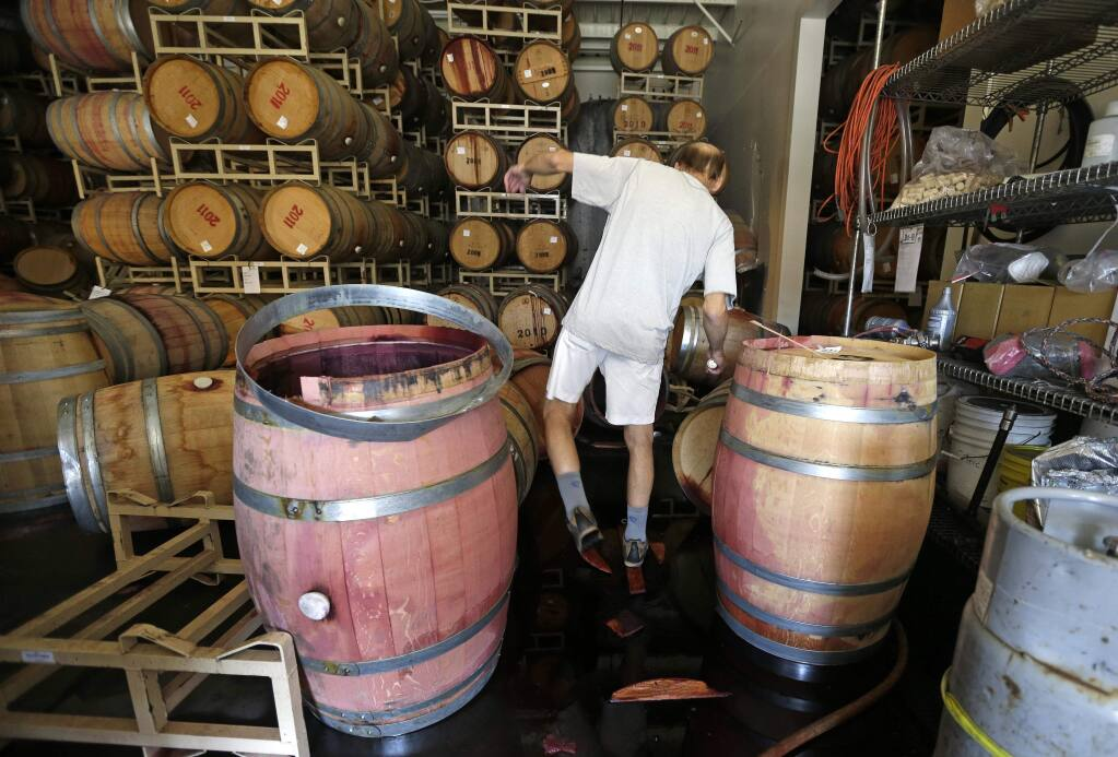 Winemaker Tom Montgomery walks through wine to see the damage following an earthquake at the B.R. Cohn Winery barrel storage facility Sunday, Aug. 24, 2014, in Napa, Calif. (AP Photo/Eric Risberg)