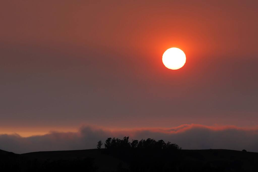 The sun begins to set behind layers of haze, a result of the recent northern California wildfires, above the hills west of Petaluma, California, on Wednesday, Aug. 8, 2018. (ALVIN JORNADA/ PD)
