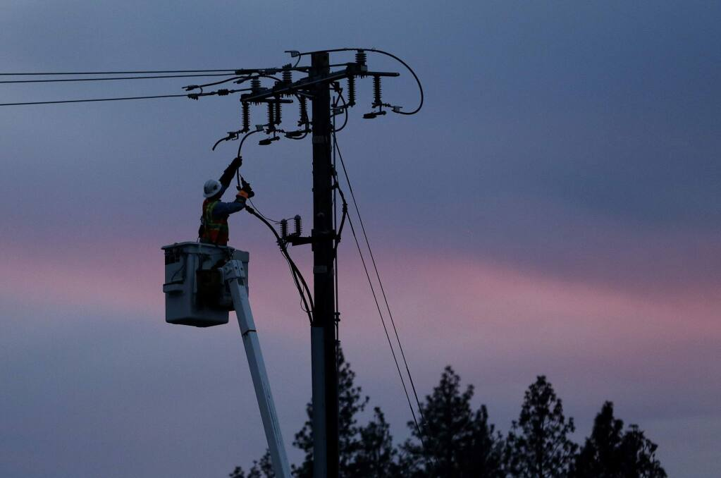 FILE - In this Nov. 26, 2018, file photo, a Pacific Gas & Electric lineman works to repair a power line in fire-ravaged Paradise, Calif. A last-minute change to a bill meant to stabilize California's electric utilities could also make it harder for local governments to buy pieces of power companies' assets and run their electric services. Critics say the change, which would provide protections for workers in case of ownership changes, could potentially make it harder for cities to buy PG&E assets. (AP Photo/Rich Pedroncelli, File)