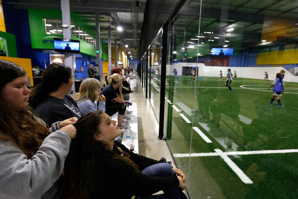 Holly Espinoza, 14, left, braids her twin sister Amanda's hair as they watch women's soccer league action on one of the Sports City indoor fields at the Epicenter sports complex in Santa Rosa, California on Thursday, October 13, 2016. (Alvin Jornada / The Press Democrat)
