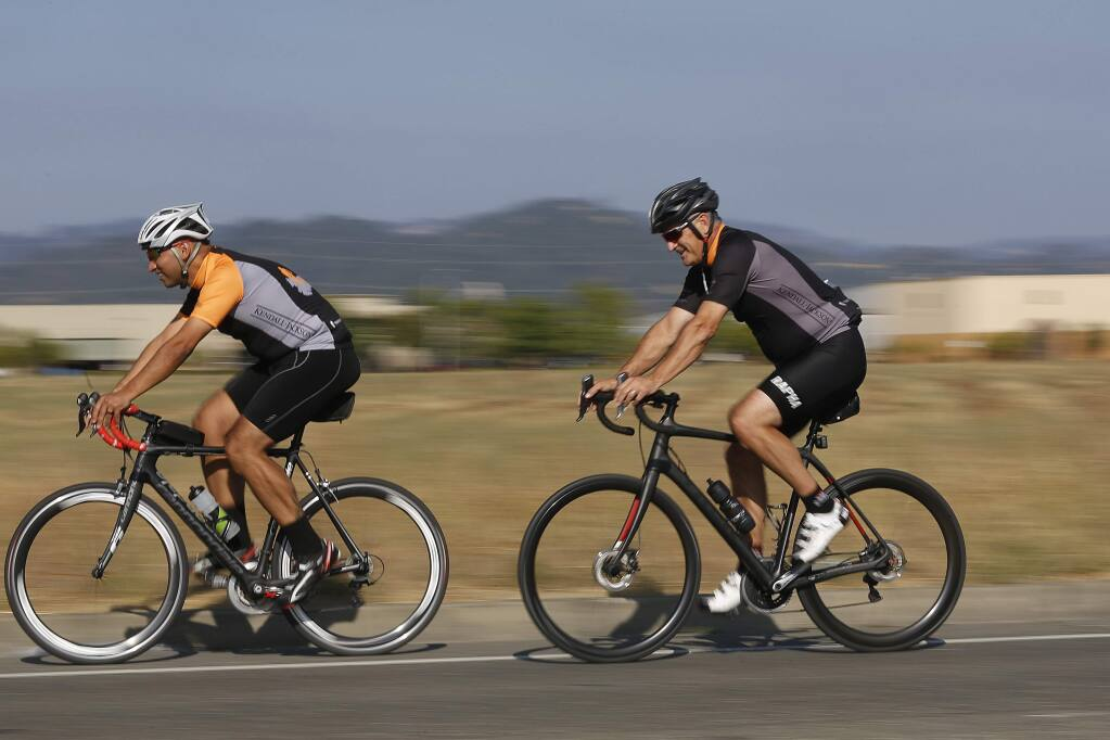 Rick Tigner, right, CEO of Jackson Family Wines, rides after work with co-workers in Santa Rosa on Wednesday, Aug. 15, 2018. (BETH SCHLANKER/ PD)