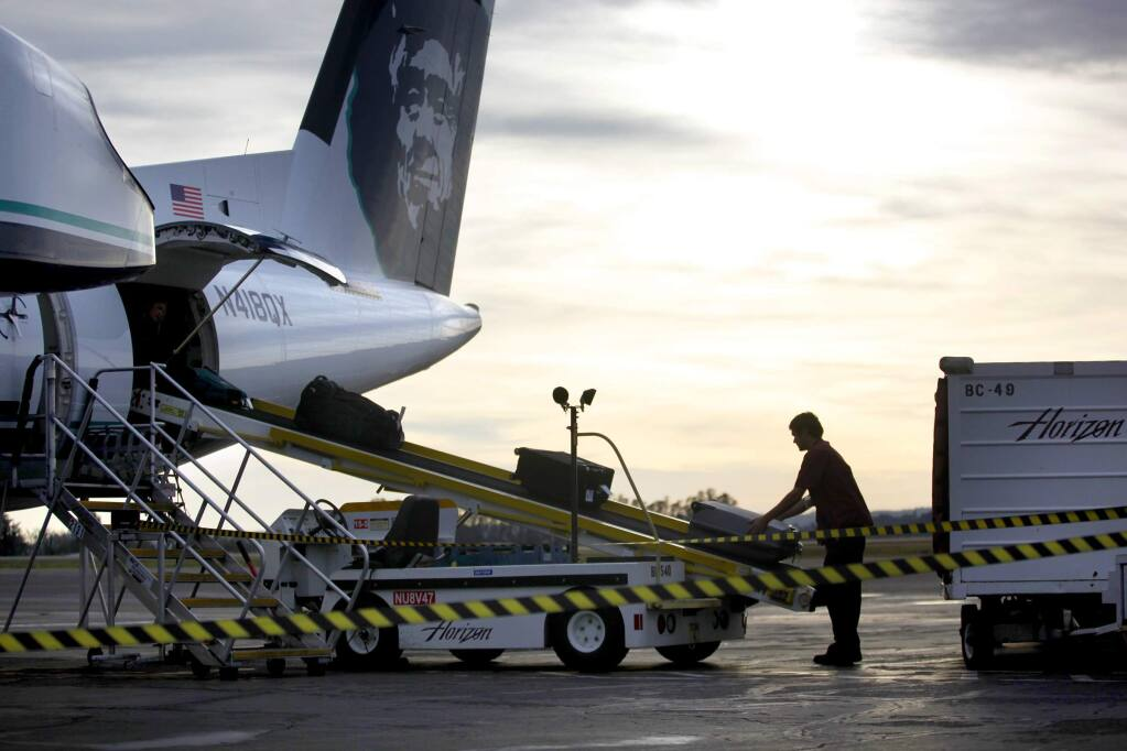 Baggage is unloaded from an Alaska Airlines flight arriving from Portland at the Sonoma County airport in 2017. (BETH SCHLANKER/ PD)