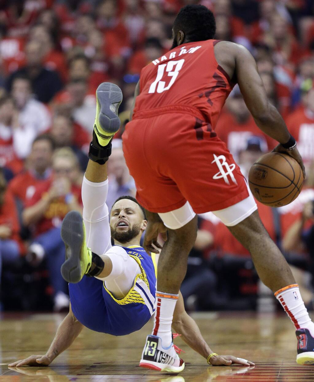 Golden State Warriors guard Stephen Curry, left, falls down after being bumped by Houston Rockets guard James Harden during the first half of Game 4 of a second-round NBA basketball playoff series, Monday, May 6, 2019, in Houston. (AP Photo/Eric Christian Smith)