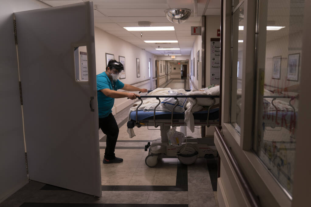 FILE - In this Feb. 19, 2021, file photo, medical transporter Adrian Parrilla moves a patient into a COVID-19 unit at Mission Hospital in Mission Viejo, Calif. (AP Photo/Jae C. Hong, File)