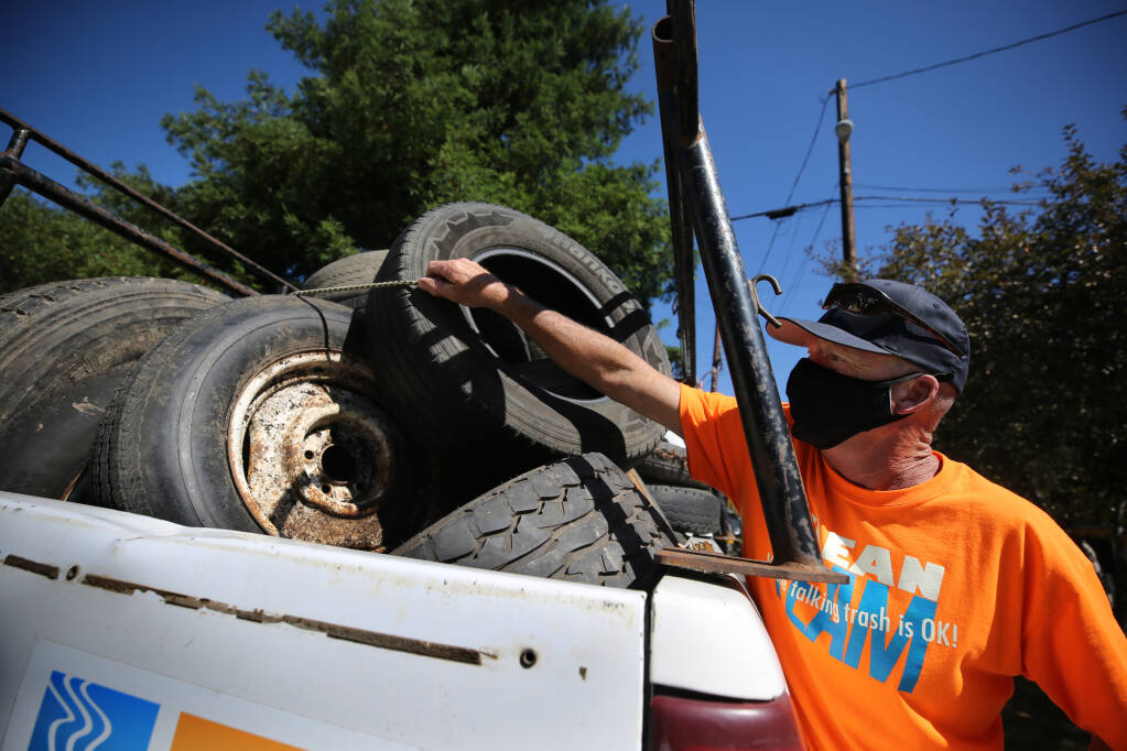 Chris Brokate, founder and executive director of Clean River Alliance, unloads abandoned tires that he collected in his truck in Guerneville on Aug. 6, 2020. (Beth Schlanker/ The Press Democrat)