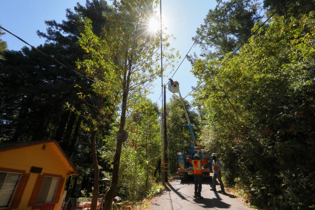 A PG&E crew works on connecting an upgraded power line to a house to a newly installed pole in Odd Fellows Park, near Guerneville, on Friday, July 24, 2020.  (Christopher Chung/ The Press Democrat)