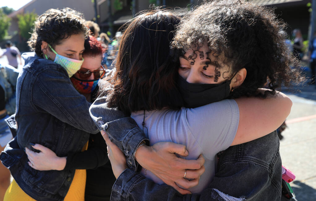 Kristen Aumoithe, left, and Amber Lucas are embraced by friends, Saturday, May 22, 2021 at the end of a poetry reading rally in front of the Santa Rosa Police Department. The two, along with Rowan Dalbey, have been accused of felony vandalism and conspiracy for smearing pig's blood on the former home of retired police officer Barry Brodd,  a police expert who testified on behalf of fired Minneapolis police officer Derek Chauvin during his murder trial in the death of George Floyd. (Kent Porter / The Press Democrat) 2021