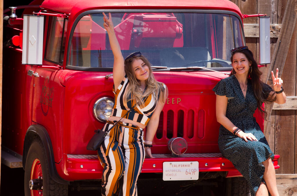 """Christina Kruglikov, left, and Olga Shigapova, both of Fremont, Calif., pose for pictures in front of an old fire truck, during the """"Wine for a Cause Flight"""" event to benefit Redwood Empire Food Bank, held at Hook & Ladder Winery in Santa Rosa, Calif., on Saturday, May 22, 2021. (Photo by Darryl Bush / For The Press Democrat)"""