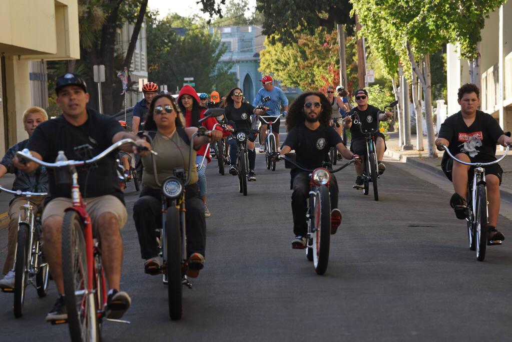 Riders head down Orchard Street to make a pit stop in downtown at the Russian River Brewing Company to allow some riders to pick up a few beers before heading to the taco trucks in the Roseland neighborhood during Santa Rosa Taco Tuesday Bike Ride in Santa Rosa on Tuesday, July 13, 2021. (Erik Castro/for The Press Democrat)