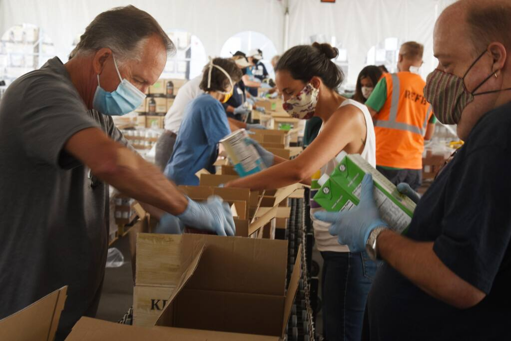 From left, John Sawyer, Rachel Hundley and Chris Hightower were part of a group of elected officials packaging food at Redwood Empire Food Bank in Santa Rosa on Saturday, Aug. 8, 2020. (Erik Castro / for The Press Democrat)
