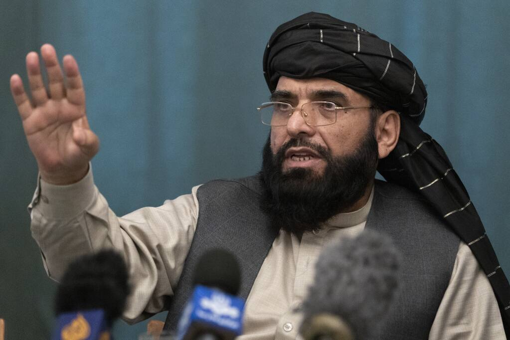 FILE - In this March 19, 2021 file photo, Suhail Shaheen, Afghan Taliban spokesman and a member of the negotiation team gestures while speaking during a joint news conference in Moscow, Russia. In an interview with The Associated Press Thursday, July 22, 2021, Shaheen said the insurgent movement does not want to monopolize power, but there won't be peace until there is a new, negotiated government in Kabul and Afghan President Ashraf Ghani is removed. Shaheen said women will be allowed to work, go to school, and participate in politics but will have to wear the hijab, or headscarf. (AP Photo/Alexander Zemlianichenko, Pool, File)