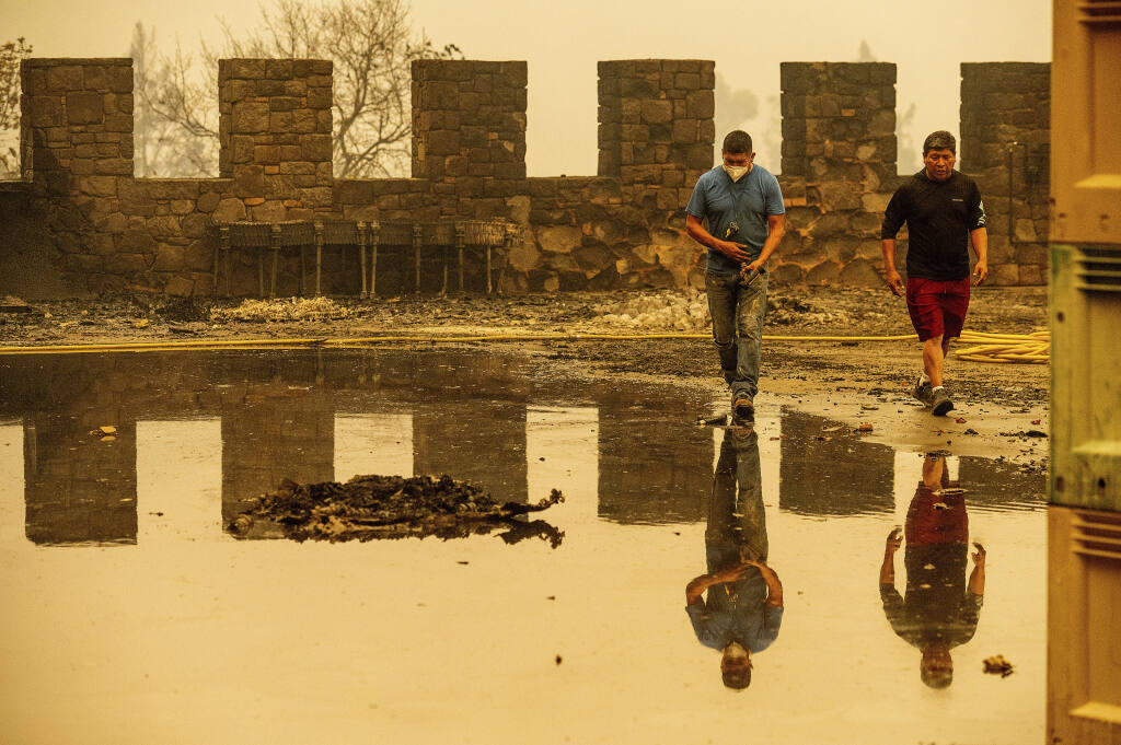 Winery worker Carlos Perez, left, walks, Monday, Sept. 28, 2020, in Calistoga, Calif., through Castello di Amorosa, which was damaged in the Glass Fire. Perez helped build the wine cellar that was scorched in the blaze. (AP Photo/Noah Berger)