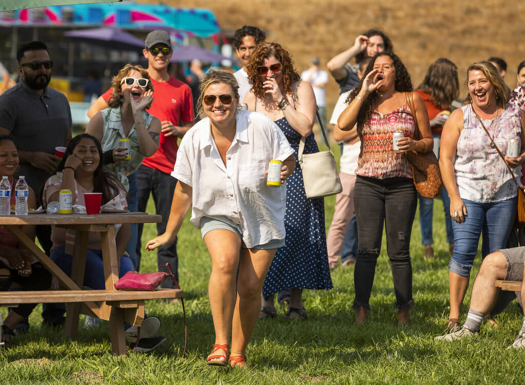 Meghan Heron, front, laughs while employees of Stark's Steak & Seafood cheer after her name was called in $1,000 raffle. The Stark Reality Restaurants closed their seven Sonoma County restaurants for a party and raffle for vaccinated employees at Cloverleaf Ranch in Santa Rosa on Wednesday, September 1, 2021.  (Photo by John Burgess/The Press Democrat)