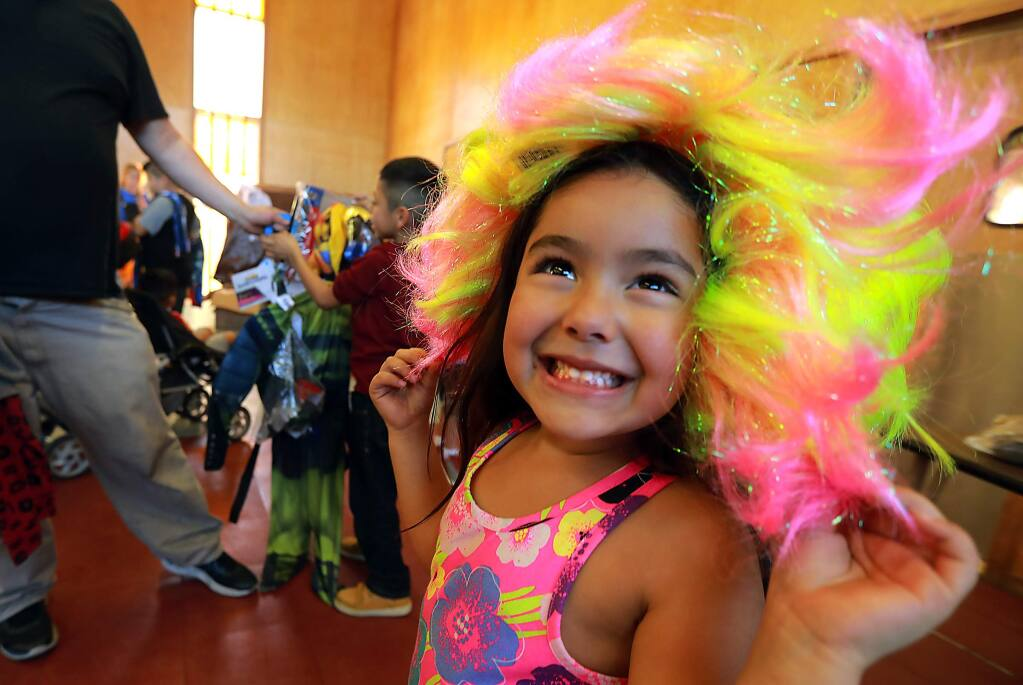 Neveah Benjamin, 4, dazzles her parents in a multi-colored wig at the Santa Rosa Christian Church on Friday. The Santa Rosa Police Department sponsored the Halloween costume drive. (photo by John Burgess/The Press Democrat)