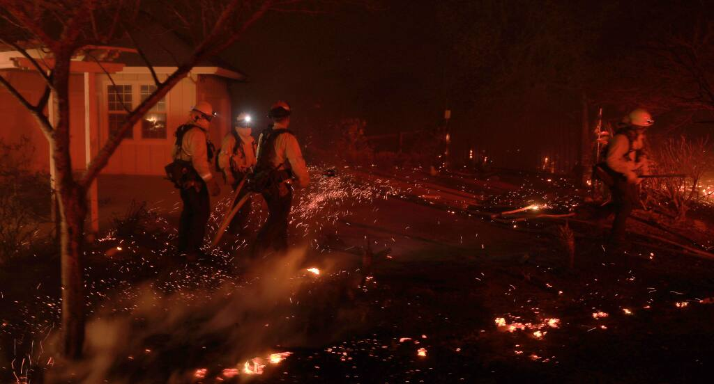 Firefighters prevent the spread of embers at a house fire on Chalk Hill Road, due to the Kincade fire blowing up with the wind, Sunday, October 27, 2019. (Kent Porter / The Press Democrat)