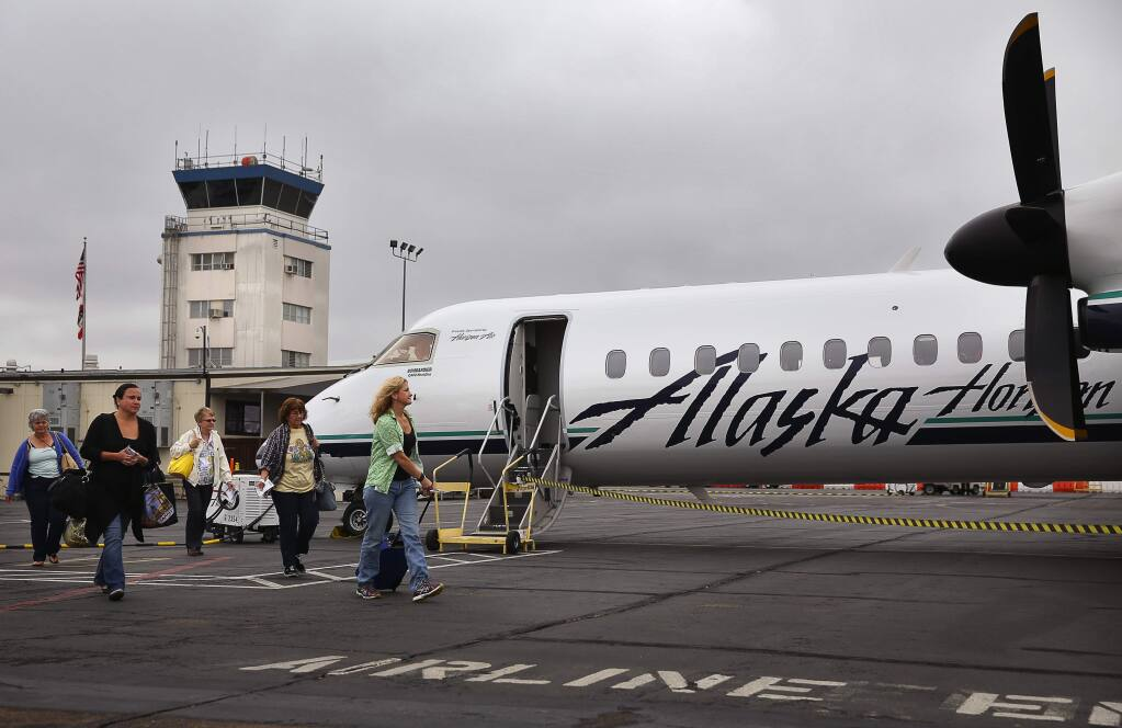 Passengers board their Alaska Airlines flight bound for Los Angeles, at the Charles M. Schulz-Sonoma County Airport, in Santa Rosa, on Friday, August 21, 2015. (Christopher Chung/ The Press Democrat)
