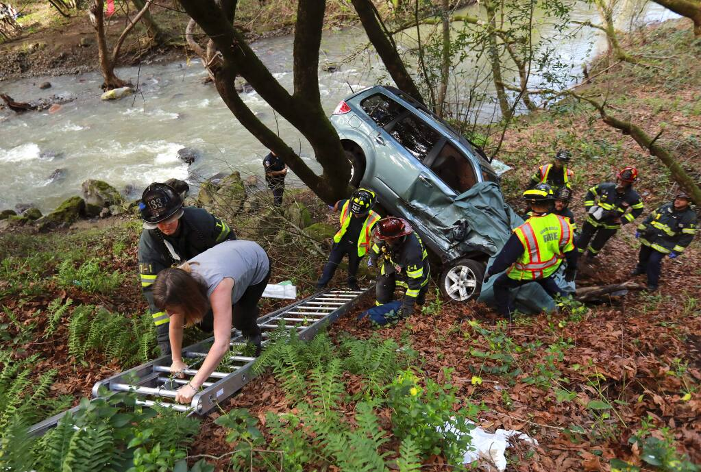 Santa Rosa firefighters remove a woman driver through the front window after an accident that pinned the vehicle between two trees near above Santa Rosa creek on Montgomery Dr. on Tuesday afternoon, February 14, 2017. (John Burgess/The Press Democrat)