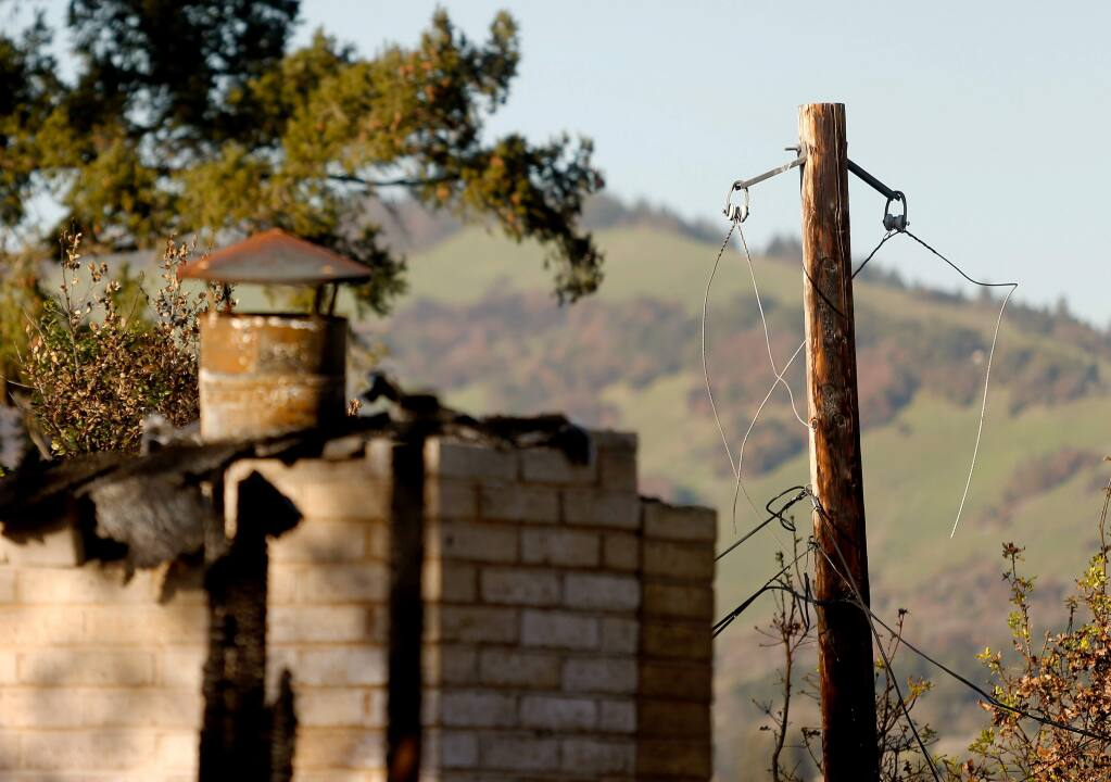 A burned utility pole, at right, still stands in front of the house Sam and Kathi Flores rented on Sullivan Way in Santa Rosa on Friday, Feb. 2, 2018. While the Flores's home burned down the same night as the Tubbs fire, Santa Rosa fire investigators determined that PG&E power lines impacted by heavy winds ignited the flames that burned their house down. (ALVIN JORNADA/ PD)