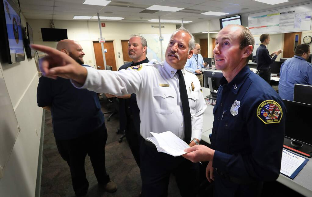 At the county center in Santa Rosa, Santa Rosa Fire Chief Tony Gossner and Santa Rosa Fire Department Assistant Fire Marshal Paul Lowenthal, watch as responses come in from the public, Wednesday, Sept. 12, 2018, as five target locations using the federal Wireless Emergency Alerts system were tested. Background from left are Neil Bregman, Santa Rosa's emergency preparedness coordinator and District 4 Supervisor James Gore. (Kent Porter / The Press Democrat)