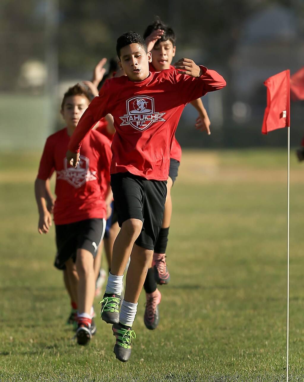 Older kids of the Tahuichi soccer league limber up during a team practice at Elsie Allen High School, Tuesday Aug. 9, 2016. (Kent Porter / The Press Democrat) 2016