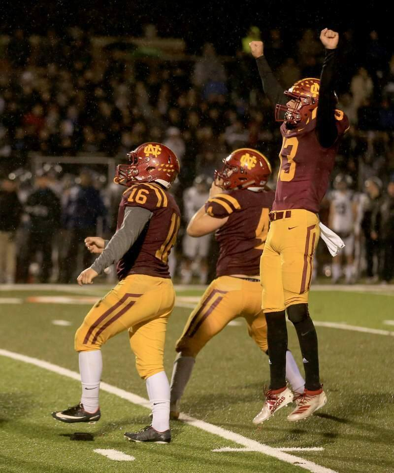 KENT PORTER/THE PRESS DEMOCRATEthan Kollenborn (16) watches his game-winning field goal sail through the uprights as John Headley, right, and Shane Moran celebrate as Cardinal Newman beats Marin Catholic 13-10 to win the NCS championship.