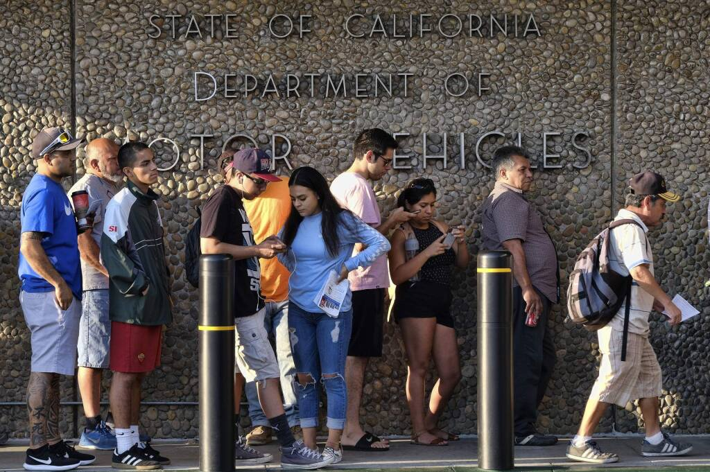FILE - In this Aug. 7, 2018, file photo, people line up at the California Department of Motor Vehicles prior to opening in the Van Nuys section of Los Angeles. The California DMV's new voter registration program is confusing to voters and full of technical difficulties according to the findings of an audit released by the state Department of Finance, Friday, Aug. 9, 2019.(AP Photo/Richard Vogel, File)