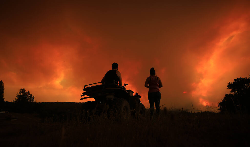 Julio and Amairani watch the Walbridge fire creep down the mountain, Wednesday, Aug. 19, 2020 near their home off Mill Station Road in Healdsburg.  (Kent Porter / The Press Democrat) 2020