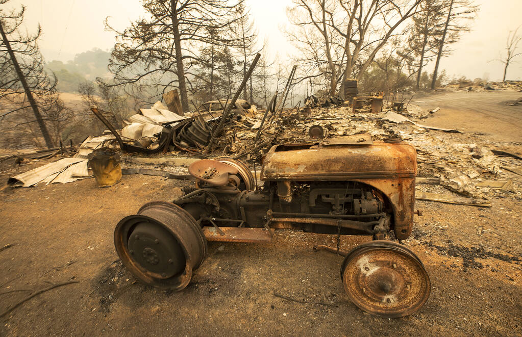 An old tractor rests on the site of a home razed by the Glass Fire on Los Alamos Rd.on Friday, October 2, 2020. (Photo by John Burgess/The Press Democrat)