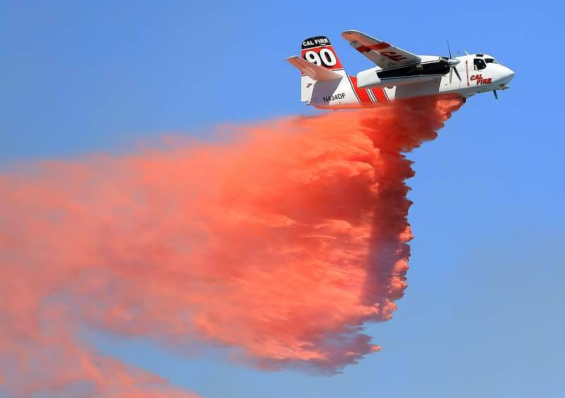A Cal Fire air tanker drops retardant on a brush fire at the old county landfill in Healdsburg, Tuesday June 18, 2013. (Kent Porter / Press Democrat) 2013