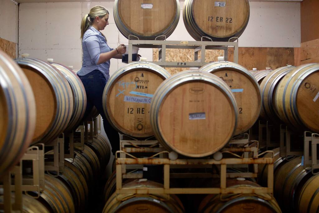 Winemaker Erica Stancliff tops off barrels of pinot noir wine at Furthermore Wines in Sebastopol, California, on Monday, June 12, 2017. (Alvin Jornada / The Press Democrat)