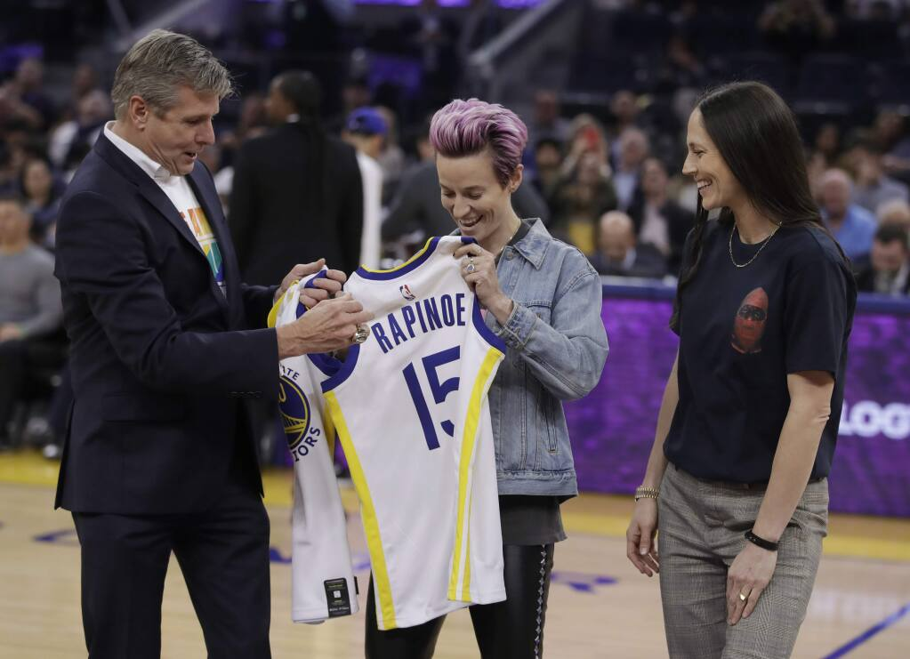 Golden State Warriors CEO Rick Welts, left, presents jerseys to soccer player Megan Rapinoe (15) and basketball player Sue Bird, right, during the first half of the Warriors' NBA basketball game against the Phoenix Suns on Wednesday, Oct. 30, 2019, in San Francisco. (AP Photo/Ben Margot)