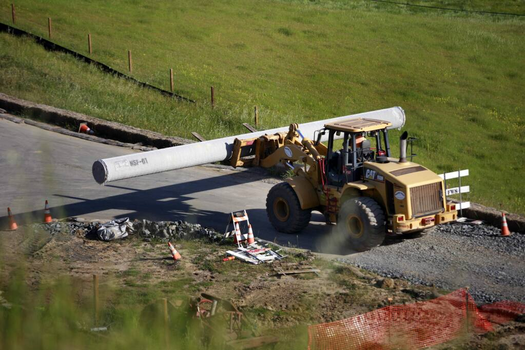 Construction workers continue to unload pipe from a flatbed trailer truck after one of the pipe pieces rolled over and killed a 33-year-old construction worker southwest of the Petaluma Blvd S exit of Hwy 101 in Petaluma, on Wednesday, April 15, 2015. (BETH SCHLANKER/ The Press Democrat)
