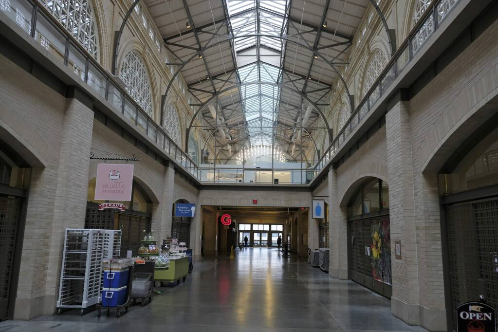 The main hallway of the Ferry Building Marketplace is mostly empty Monday, March 16, 2020, in San Francisco. Millions of California's oldest and youngest residents stayed home Monday as officials took increasingly strident steps to separate people and contain the spread of the coronavirus. Evidence that people were staying home included traffic flowing freely on some freeways that are normally congested during rush hours.(AP Photo/Eric Risberg)