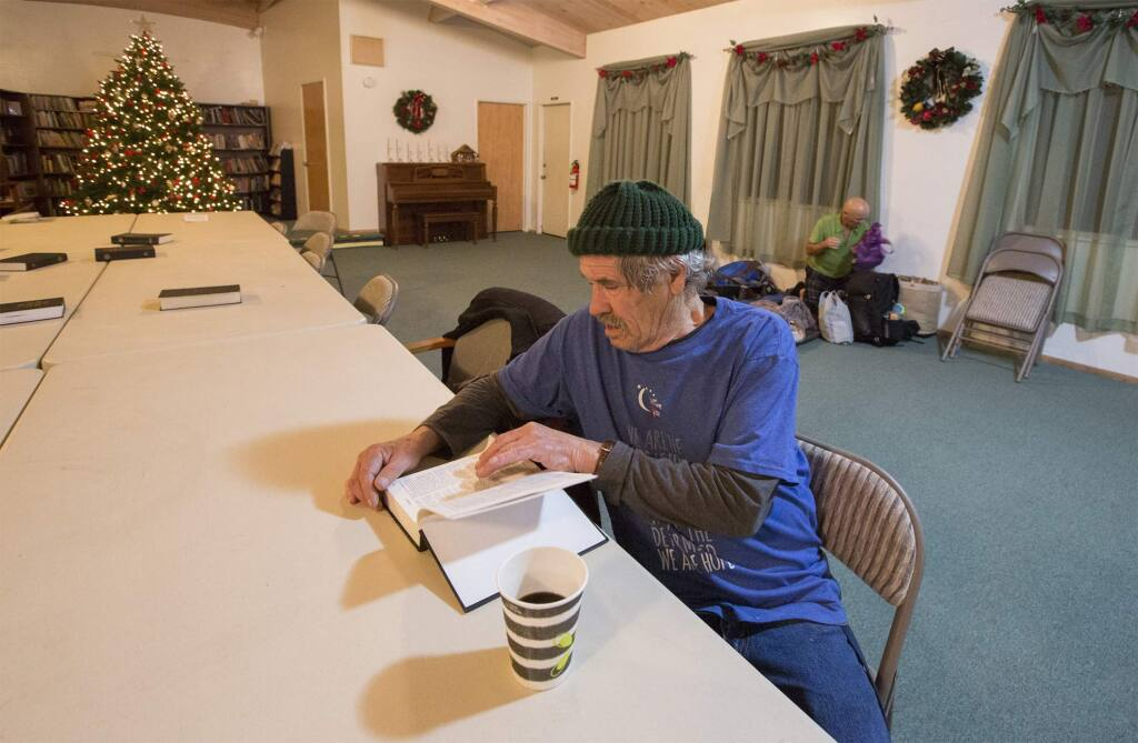 Before bedding down for the night, John Fassio has a drink and a read at the Sonoma Alliance Church. (Photo by Robbi Pengelly/Index-Tribune)