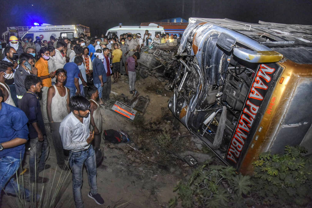 Onlookers gather near the wreckage after a bus carrying migrant workers after the lifting of coronavirus restrictions hit a delivery van on a highway near Kanpur, Uttar Pradesh state, India, Tuesday, June 8, 2021. More than a dozen people were killed. (AP Photo)