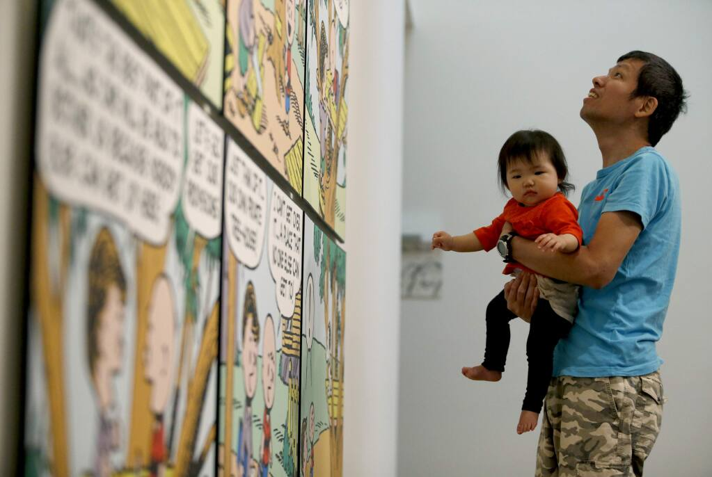 Yasutaka Yoshikawa, visiting from Japan, holds his 11-month-old daughter Sora as he looks at a Peanuts display at the Charles M. Schulz Museum on Monday, May 2, 2016 in Santa Rosa, California . (BETH SCHLANKER/ The Press Democrat)