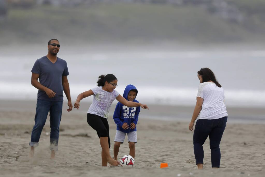Taylor Cager, 9, ties to score a goal as she plays soccer with her her brother, Sean, 8, father, Brandon, and her mother, Julie, at Doran Regional Park on Monday, March 16, 2015 in Bodega Bay, California . (BETH SCHLANKER/ The Press Democrat)