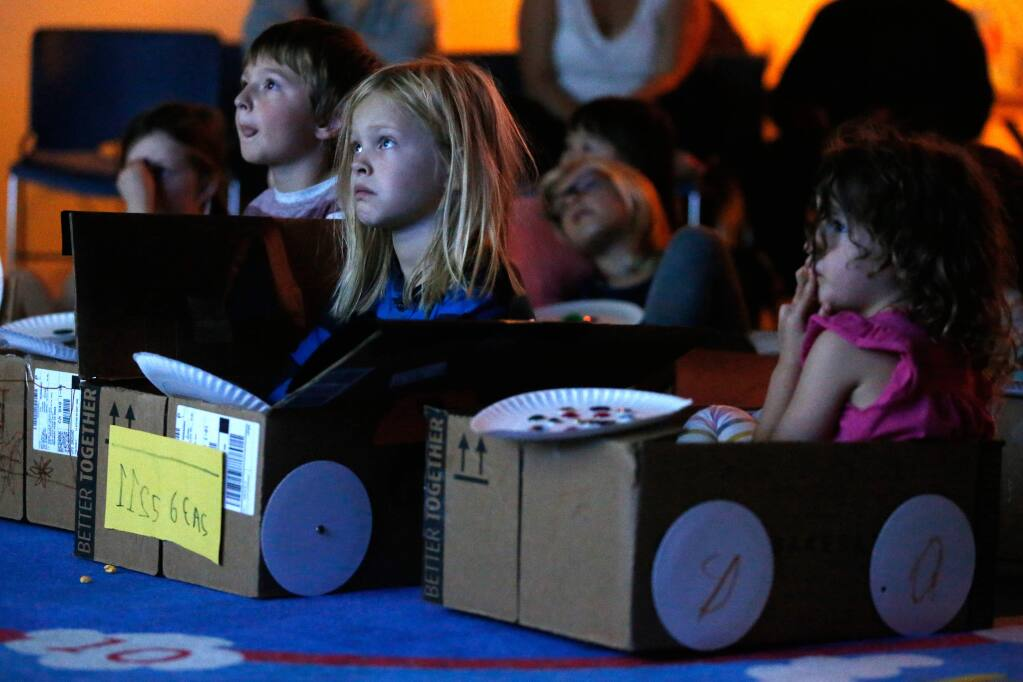 Ezra Lunden, 7, second from left, and other children sit in boxes decorated as cars for a 'drive-in' movie at Petaluma Regional Library in Petaluma, California, on Friday, November 2, 2018. (Alvin Jornada / The Press Democrat)
